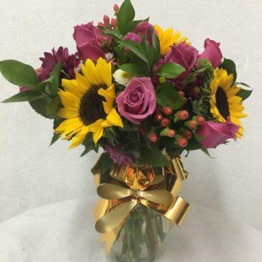Arreglo Floral con 18 Rosas Moradas, Girasoles y Gerberas